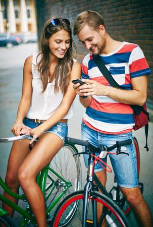 Young couple on bicycles using cellphone outdoors photo