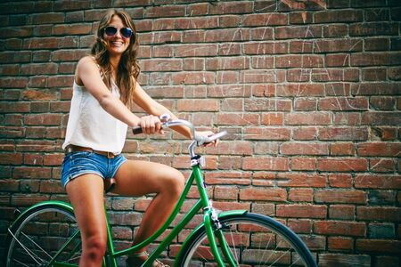 Female bicyclist in eyeglasses standing against brick wall photo