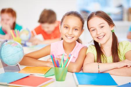 preteen girl: Friendly schoolgirls looking at camera in school Stock Photo