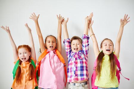 niños felices: Eufórico niños con mochilas para levantar los brazos Foto de archivo