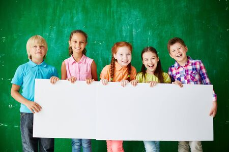 schoolkids: Friendly schoolkids with blank paper standing against blackboard Stock Photo