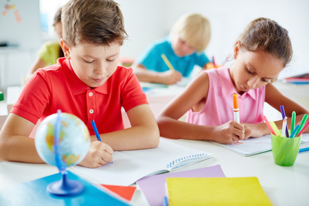 schoolchildren: Friendly schoolchildren drawing with highlighters at lesson Stock Photo