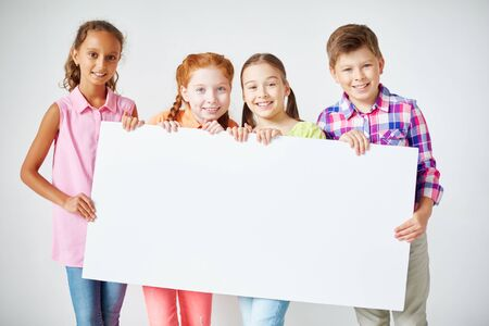 schoolkids: Happy schoolkids holding blank paper and looking at camera Stock Photo