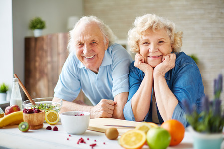 Hombre mayor feliz y una mujer mirando a la cámara en la cocina