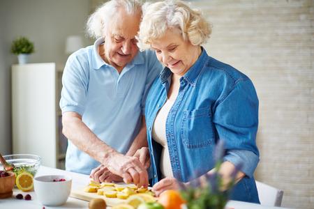 cocina antigua: Hombre mayor feliz y mujer cortar las frutas en la cocina