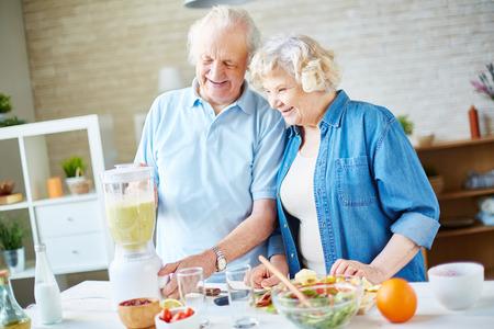 cocina vieja: Mayores felices que cocinan batido de frutas Foto de archivo