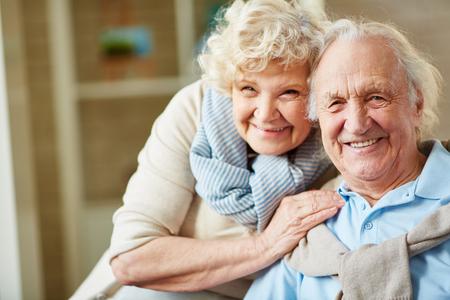 donna innamorata: Affettuoso uomo anziano e la donna guardando la fotocamera