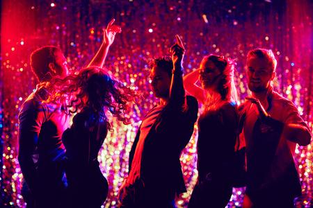 Amigos jóvenes dinámicos bailando en la fiesta de discoteca Foto de archivo
