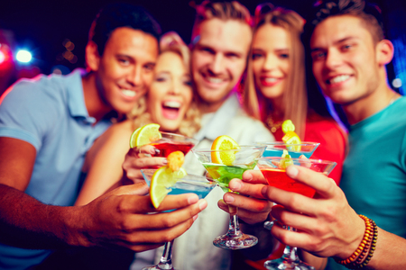 jovenes tomando alcohol: Grupo de j�venes amigos brindando con c�cteles