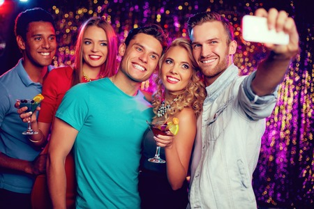 company party: Company of cheerful friends making selfie at party