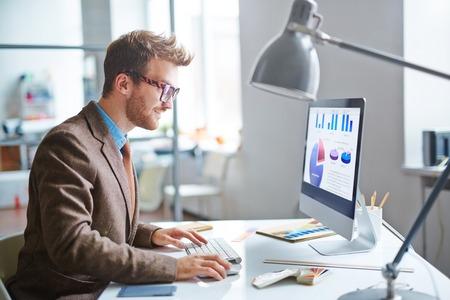 Oficinista joven moderna que usa el ordenador