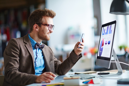 Young employee with cellphone sitting in front of computer