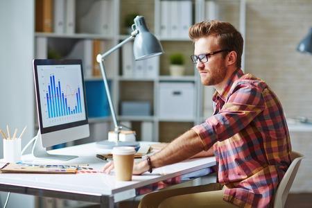 trabajando en computadora: Hombre joven que mira la carta financiera que refleja los cambios en el desarrollo del mercado