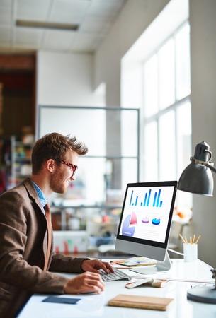Empleado joven moderno análisis de datos financieros en la oficina