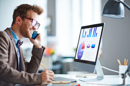 Businessman speaking on the phone and looking at computer screen with chart and diagrams