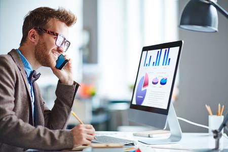 llamando: Hombre de negocios hablando por teléfono y mirando la pantalla del ordenador con la carta y diagramas