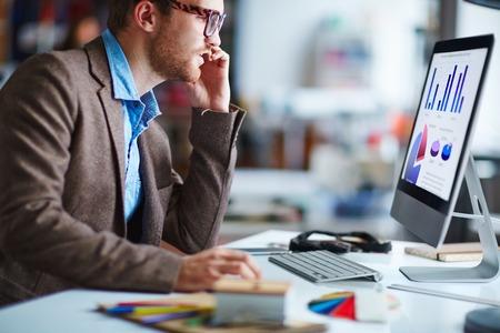 Mannelijke kantoor werknemer zit in de voorkant van de computer