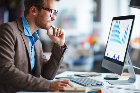 trabajando en computadora: Hombre trabajador de oficina mirando la pantalla del ordenador con los datos Foto de archivo