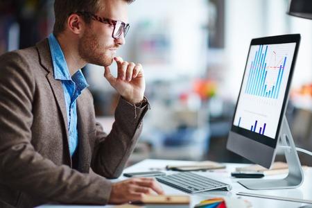 ordinateur bureau: Homme employé de bureau en regardant l'écran de l'ordinateur avec des données