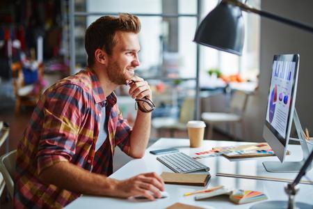 Hombre feliz mirando la pantalla del ordenador con los datos al tiempo que la decisión final Foto de archivo