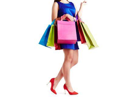 paperbags: Shopaholic in blue dress holding several multi-color paperbags Stock Photo