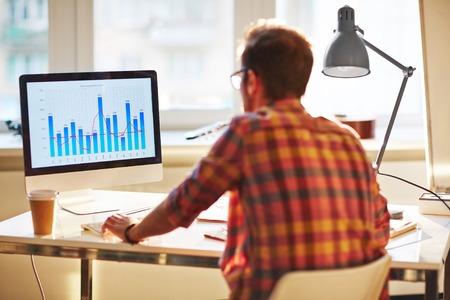 ホワイト カラー労働者のオフィスで金融チャートを分析