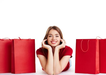 paperbags: Young shopper looking at camera between red paperbags Stock Photo