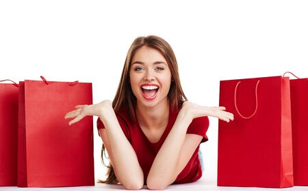 Ecstatic young woman looking at camera between red paperbags Stock Photo
