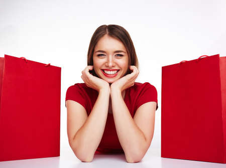 paperbags: Smiling girl looking at camera between two red paperbags