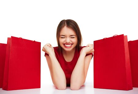 paperbags: Joyful girl with expression of triumph lying between red paperbags Stock Photo