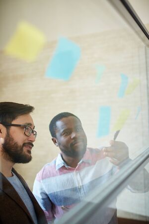 business ideas: African businessman presenting his plan to colleague Stock Photo