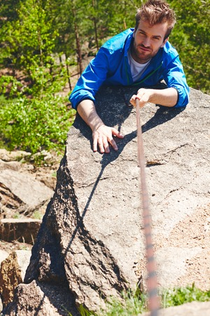activewear: Young sportsman ascending cliff of mountain