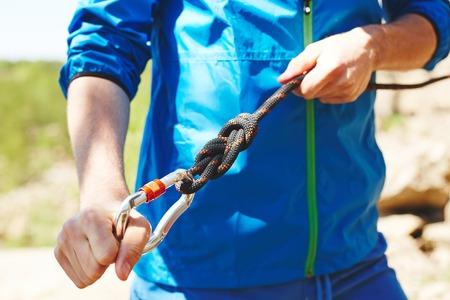 carabiner: Sportsman preparing carabiner for climbing