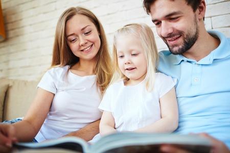 mom dad: Feliz pareja joven y su hija la lectura en casa Foto de archivo