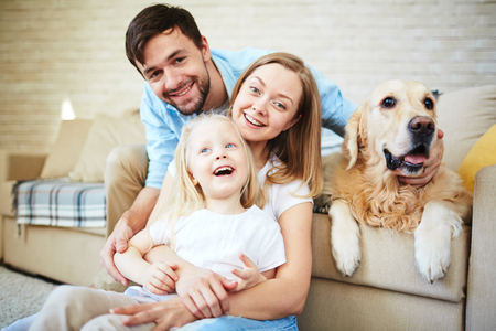 Familia que tiene resto en casa feliz con su mascota