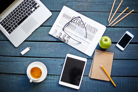 blank newspaper: Technological devices, cup of tea, green apple, newspaper, eyeglasses and notebook with pencil on workplace