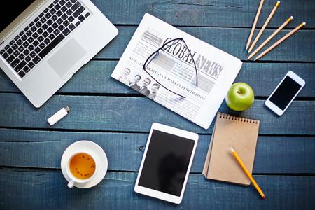 Technologische hulpmiddelen, kopje thee, groene appel, krant, brillen en notebook met potlood op de werkplek Stockfoto