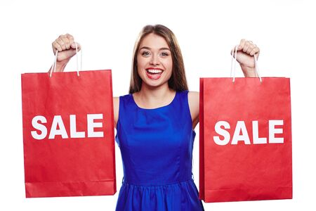 paperbags: Happy woman with red paperbags announcing sale
