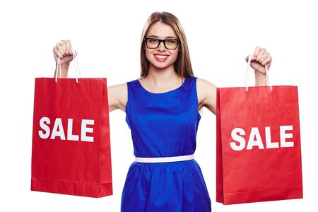 paperbags: Pretty girl in blue dress and eyeglasses holding paperbags announcing sale