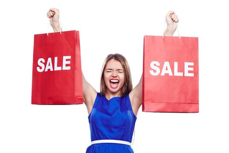 paperbags: Young woman expressing gladness while holding paperbags in raised hands Stock Photo