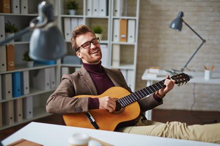 canto: Hombre de negocios joven que toca la guitarra que canta en el lugar de trabajo en la oficina Foto de archivo