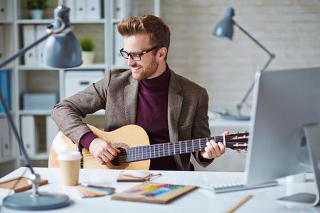 musico: joven hombre de negocios moderno tocando la guitarra en el lugar de trabajo