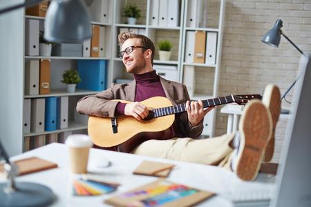 bel homme: Handsome d'affaires jouant de la guitare dans le bureau apr�s le travail