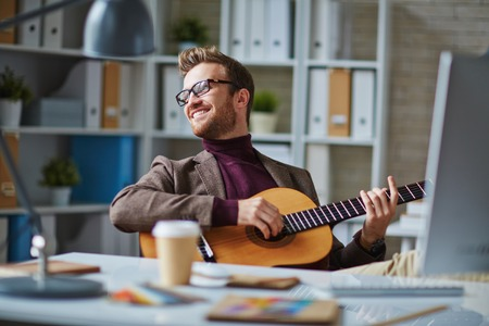 hobbies: Handsome businessman playing the guitar by desk in office