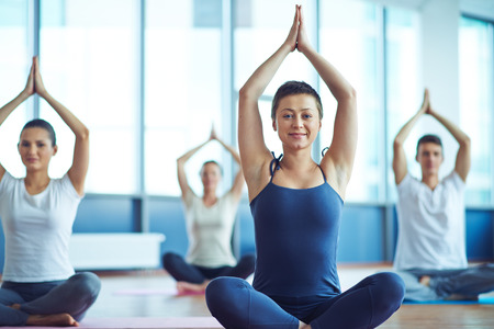 ejercicio: Mujer feliz y activa haciendo ejercicios de yoga en el fondo de sus alumnos