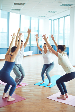 knees bent: Sporty people standing on mats with stretched arms and bent knees