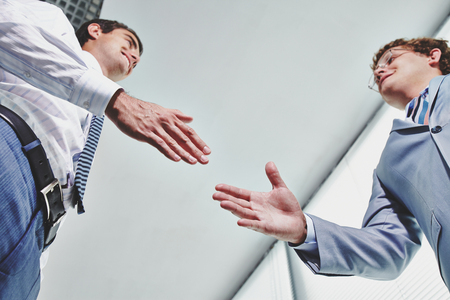 business  deal: Two young businessmen greeting one another by handshake Stock Photo