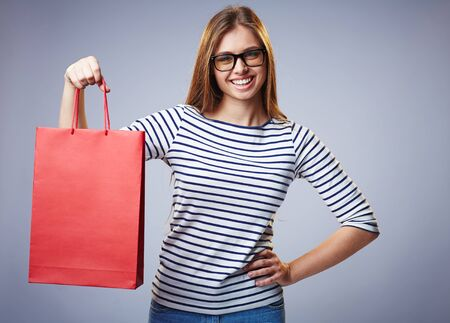 paperbag: Pretty shopper showing red paperbag and looking at camera