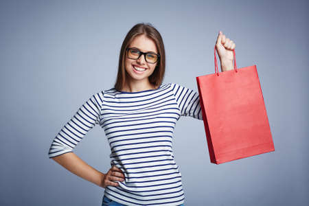 shopper: Happy young shopper with red paperbag looking at camera