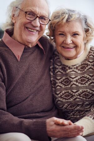 old couple: Senior husband and wife looking at camera with smiles